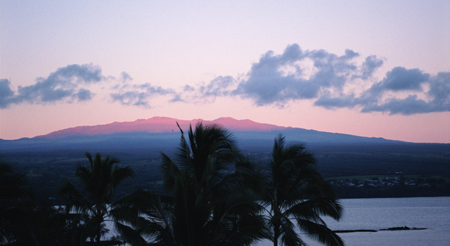 From Hilo City, Mauna Kea is seen reflected in red in the morning sun.